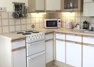 Kitchen rear - Fully equipped kitchen with hob, grill and oven, microwave, kettle and toaster