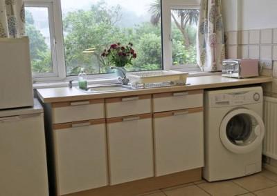 Kitchen front view - Kitchen sink area, with freezer, fridge, washing machine and toaster